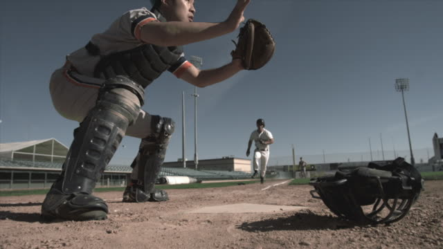 SLO MO LA WS Baseball player sliding into home plate as catcher catches ball and tags him / Lancaster, California, USA