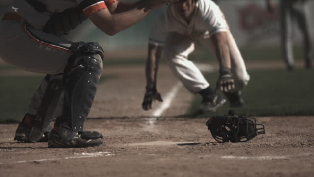 stockvideo's en b-roll-footage met slo mo ms baseball player sliding into home plate as catcher catches ball and tags him / lancaster, california, usa - honkbal teamsport