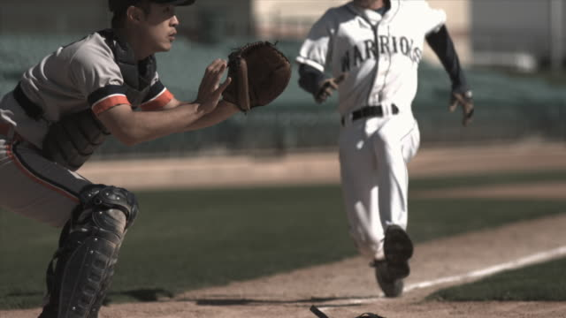SLO MO MS Baseball player sliding into home plate as catcher catches ball and tags him / Lancaster, California, USA