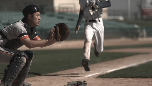 slo mo ms baseball player sliding into home plate as catcher catches ball and tags him / lancaster, california, usa - 野球ボール点の映像素材/bロール