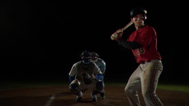a baseball player swings at a pitch and misses. - einen baseball schlagen stock-videos und b-roll-filmmaterial