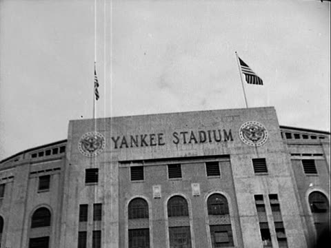 Baseball players changing sides on field during professional MLB game / facade and gate 6 entrance of Yankee Stadium in the Bronx on game day /...