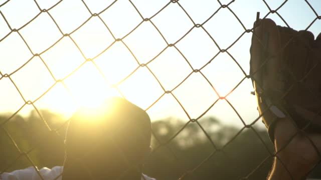 vídeos de stock e filmes b-roll de baseball players during practice in sunset - luva peça de roupa