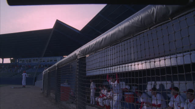 Baseball players in a dugout rush to the fence to cheer on their team as the stadium crowd stands and claps.