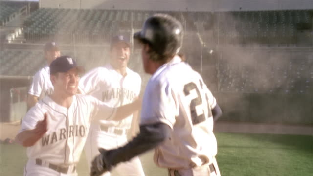 slo mo cu pan baseball players in home base / lancaster, california, usa - home run stock-videos und b-roll-filmmaterial