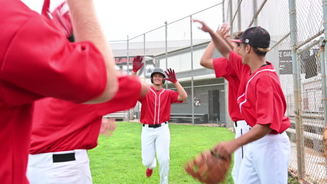 baseball teammates congratulating scoring player - baseball player stock videos & royalty-free footage