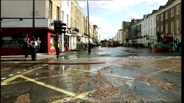 Basement flats flooded in Thames Water leak ENGLAND London Victoria EXT Fire fighters attending to flooded road Water logged street corner scattered...