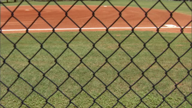 Bases first second pitcher's mound on baseball diamond w/ chain link fencing in silhouette FG Little League Closed off barred from restrained...