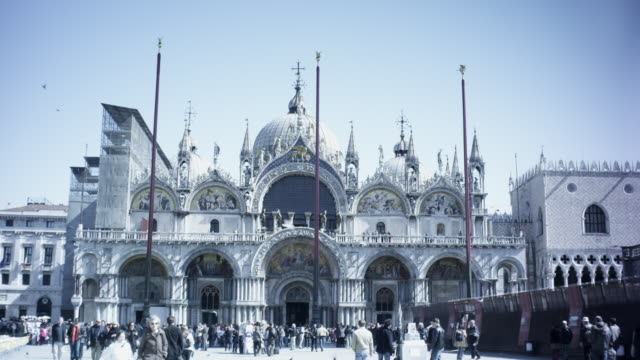 basilica cattedrale patriarcale di san marco (saint mark's basilica), day-busy with people and pigeons in front of the basillica from the view of st. mark's square - catholicism stock videos & royalty-free footage
