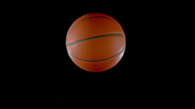 slo mo ld basketball bouncing off a black surface - rimbalzare video stock e b–roll