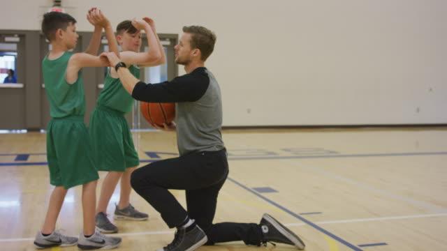 vídeos de stock, filmes e b-roll de treinador de basquete, mostrando meninos tiro a técnica apropriada - treinador