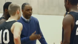 A basketball coach talking to his players in a huddle before a game