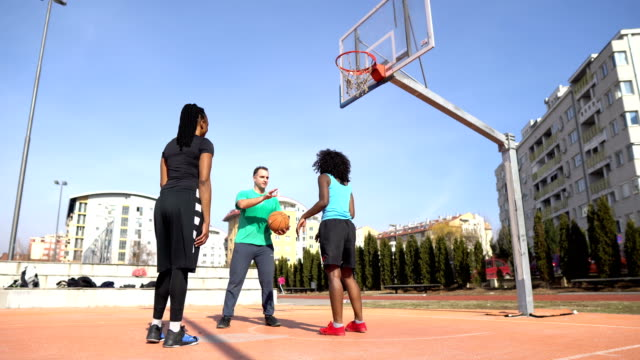 女子選手とバスケットボールコーチ - ショットを決める点の映像素材/bロール