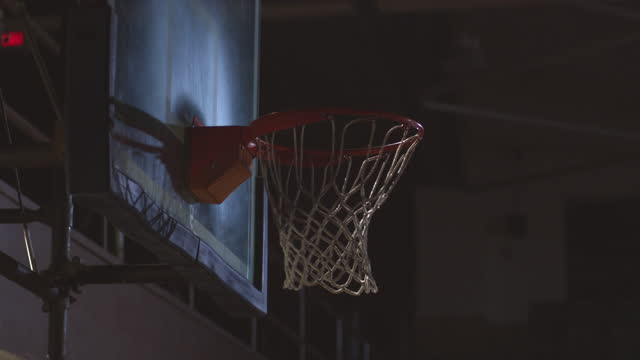 SLO MO. A basketball dances around the rim of the hoop and goes in.