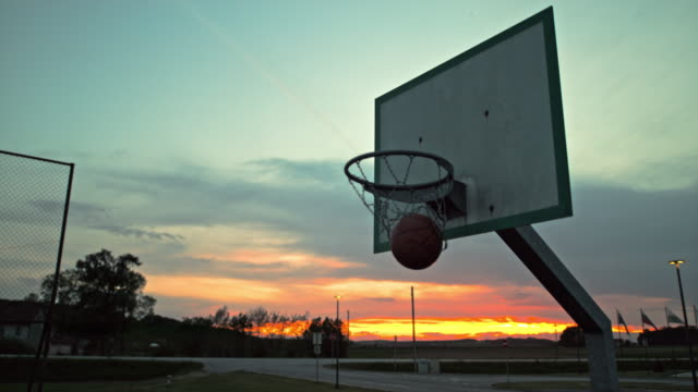 vidéos et rushes de ms super slow motion basket-ball tombant dans le cerceau sur le terrain de basket-ball extérieur au crépuscule - terrain de jeu
