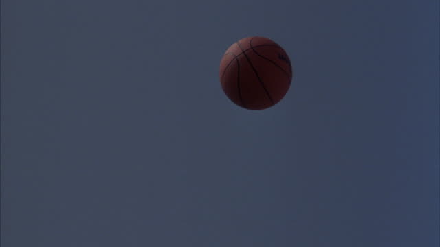 A basketball flies through the air into a basketball hoop.