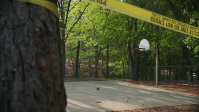 vídeos y material grabado en eventos de stock de ls basketball hoop in an empty park surrounded by police tape - patio