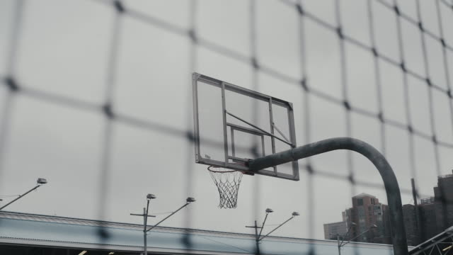 basketball hoop seen from fence against sky - net sports equipment stock videos & royalty-free footage