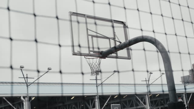 basketball hoop seen from fence against sky - courtyard stock videos & royalty-free footage