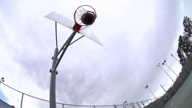 basketball making it into basketball hoop. - slow motion - filmed at 240 fps - basketball hoop stock videos & royalty-free footage
