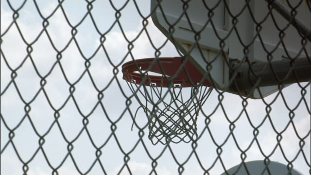 Basketball net on court behind chain link fence fencing basketball falling behind net rebound ball rolling rim falling through hoop net