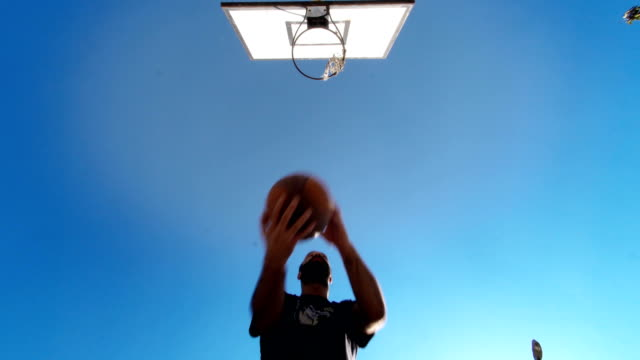 vídeos de stock e filmes b-roll de basketball player bouncing ball and taking a shot - low angle view