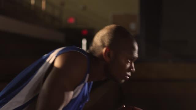 A basketball player broods on a set of bleachers.
