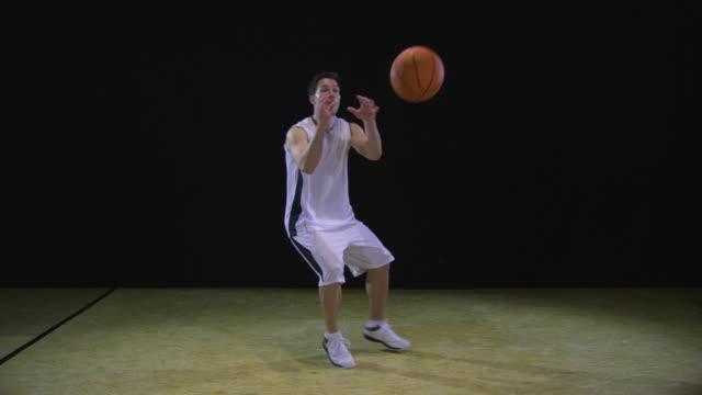 ws slo mo basketball player catching basketball and dribbling the ball / berlin, germany - スタジオ撮影点の映像素材/bロール