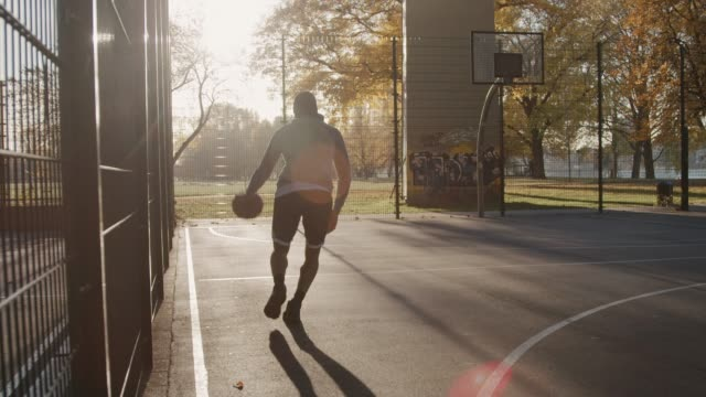 basketball player dribbling and scoring in hoop - leisure activity stock videos & royalty-free footage