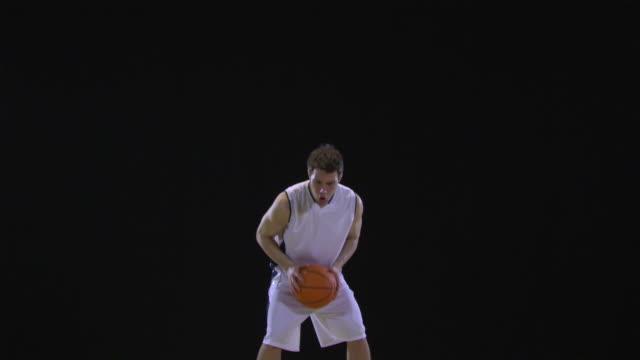 ms basketball player dribbling basketball, clenching fist / berlin, germany - スタジオ撮影点の映像素材/bロール