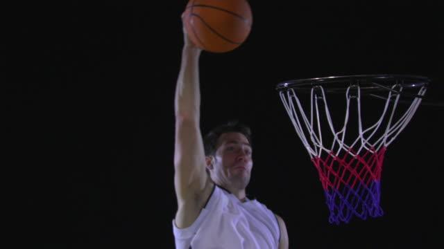 cu slo mo basketball player dunking basketball into hoop / berlin, germany - スタジオ撮影点の映像素材/bロール