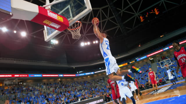 slo mo basketball player executing a slam dunk shot in the game and scoring - spiel sport stock-videos und b-roll-filmmaterial
