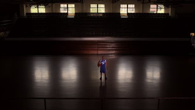 a basketball player in uniform slowly turns as he surveys an empty court. - sports court stock videos & royalty-free footage