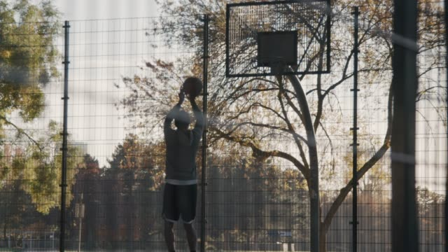 basketball player practicing on outdoor court - basketball sport stock videos & royalty-free footage