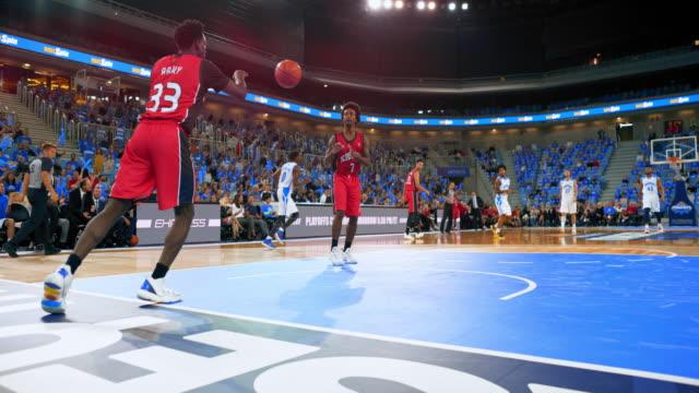 slo mo basketball player putting ball in play - avvenimento sportivo video stock e b–roll