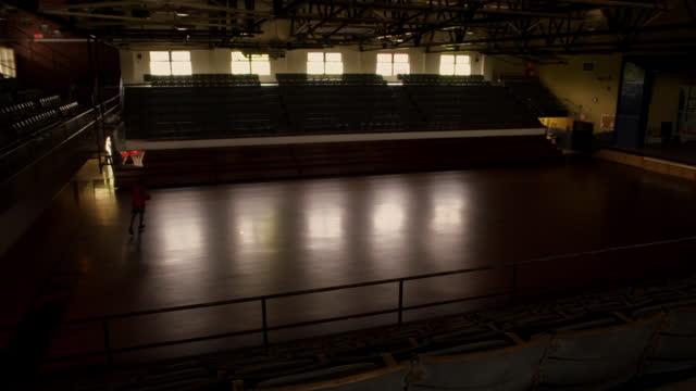 vídeos de stock, filmes e b-roll de a basketball player sinks a three pointer practicing in an empty gymnasium. - praticando