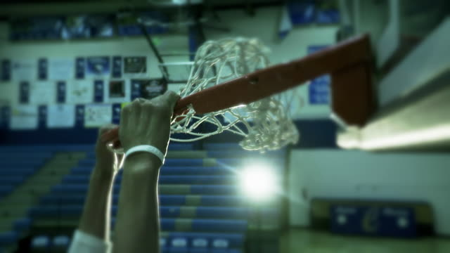 Basketball player slam dunking a basketball close up shot super slow motion