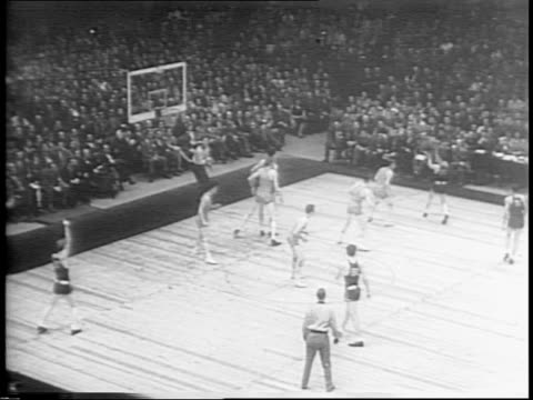 vídeos y material grabado en eventos de stock de basketball players george mikan of depaul university and bob kurland of university of oklahoma aggie stand in front of skyscrapers / oklahoma aggies... - encestar