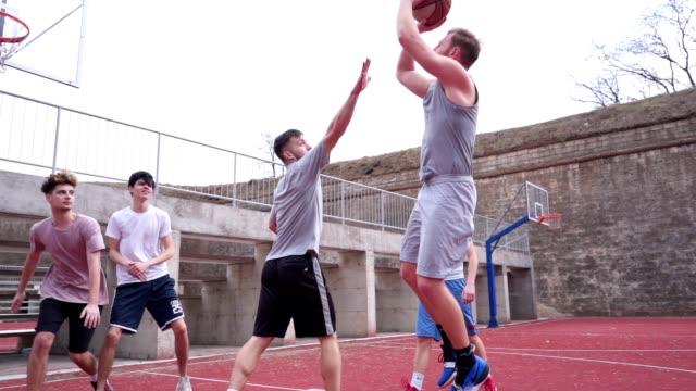 vidéos et rushes de joueurs de basketball jouant sur un tribunal extérieur - panier de basket