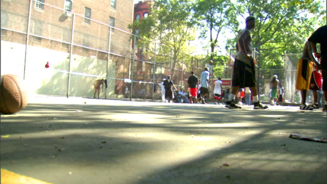 vidéos et rushes de basketball rolling out of frame on outdoor court, unidentifiable african american males playing, standing around on court bg. streetball, game - streetball