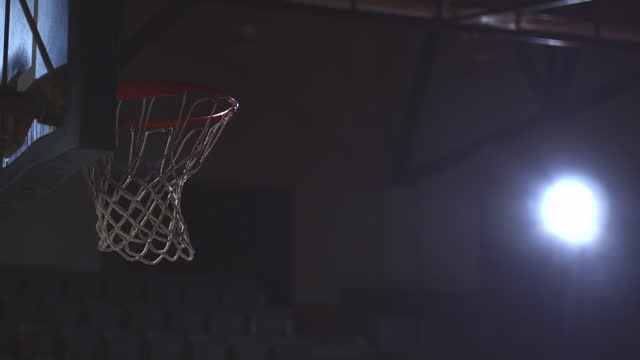 slo mo. a basketball sinks cleanly into the net. - basketball stock-videos und b-roll-filmmaterial