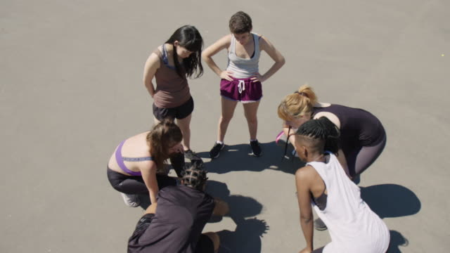 vidéos et rushes de équipe de basket-ball discutant le plan de jeu sur le court - streetball