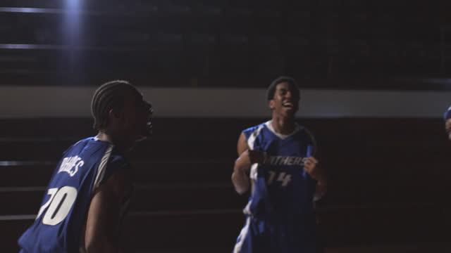 Basketball teammates celebrate on a court.