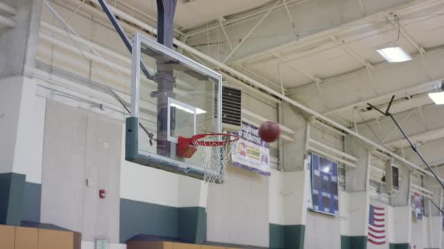 Ballons de basket-ball étant tirés sur un cerceau