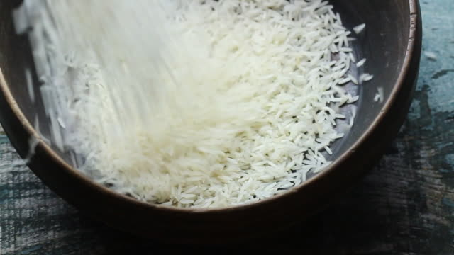 basmati rice being poured into wooden bowl - reis grundnahrungsmittel stock-videos und b-roll-filmmaterial