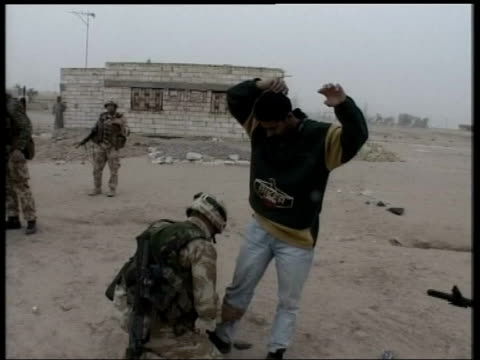 basra: ext british soldier body searching iraqi suspect cms soldier tying prisoner's wrists side prisoner kneeling beside tank with hands tied behind... - civilian stock videos & royalty-free footage
