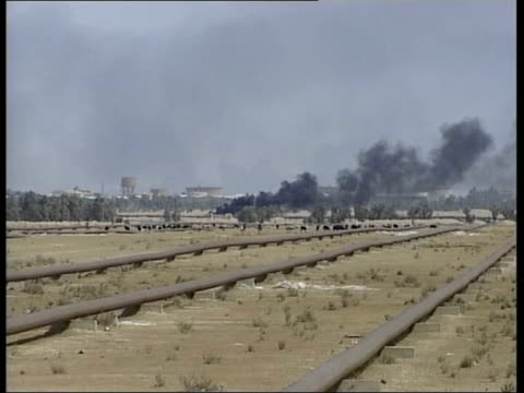 basra itn iraq nr basra ext tracking shot cars away on road towards plume of thick black smoke on horizon abandoned iraqi position at roadside track... - basra stock videos and b-roll footage