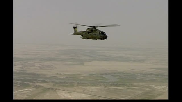 vidéos et rushes de three british soldiers killed date british merlin military helicopter in flight over desert area - bassora