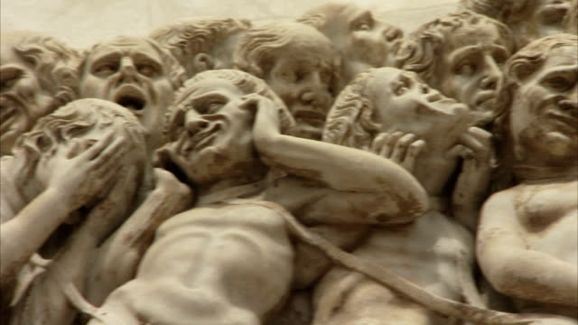Bas-relief statues depict human suffering and sorrow. Available in HD.