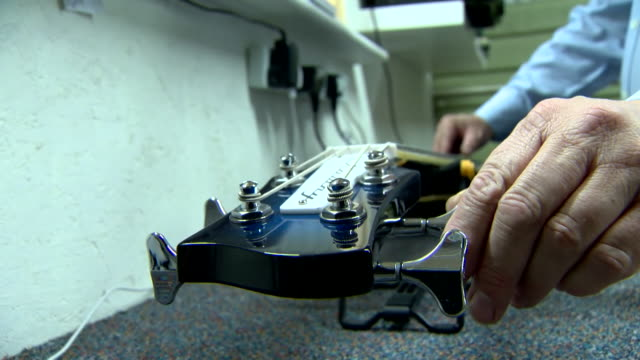 a bass guitar being tuned in a guitar shop - musical instrument string stock videos and b-roll footage